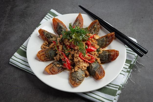 Smażona bazylia wymieszana z pikantnym jajkiem stulecia podana z ryżem gotowanym na parze i sosem rybnym chili, tajskie jedzenie.