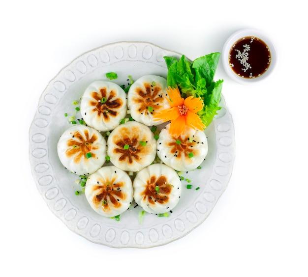 Smażona bułka na parze lub sheng jian bao wypełniona mieloną wieprzowiną i puszystą chrupiącą warzywami