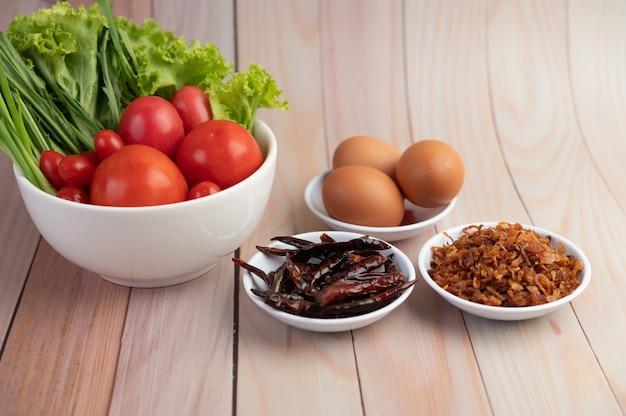 Smażona cebula, papryka, jajka, pomidory, sałatka i dymka w białej filiżance na drewnianej podłodze.