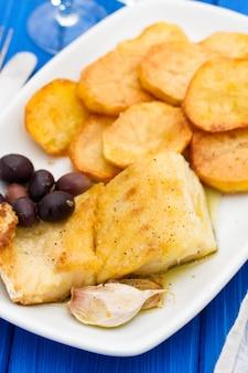 Smażona dorsz ryba z grulą na białym naczyniu