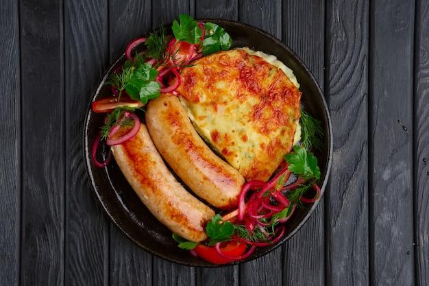 Smażona kiełbasa domowej roboty ze smażonymi puree ziemniaczanym, marynowaną cebulą i pomidorem