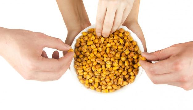 Smażona kukurydza z rękami na białym tle na białej przestrzeni