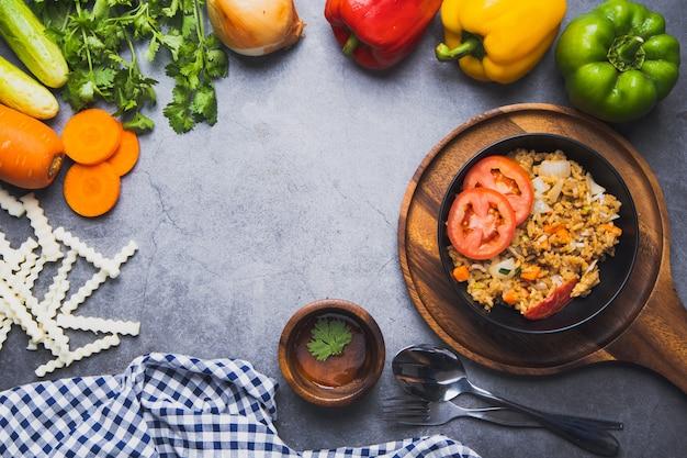 Smażona mieszanka ryżu z naturalnym odżywianiem i świeżymi warzywami na tle ciemnego cementu, czystego jedzenia i dobrego zdrowego posiłku do menu