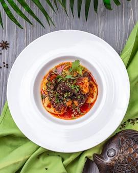 Smażona ośmiornica z warzywami zieleni ziemniaczanej pietruszki pomidorowy odgórny widok