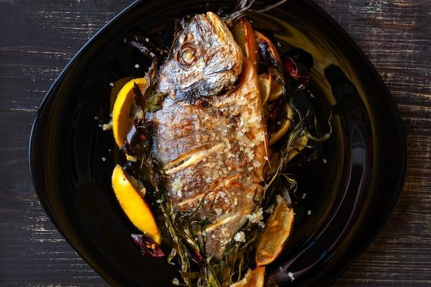 Smażona ryba dorado z cytryną i rozmarynem z bliska na czarnym tle drewnianych. zdrowe odżywianie. widok z góry