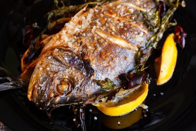 Smażona ryba dorado z cytryną i rozmarynem z bliska. zdrowe odżywianie. widok z góry