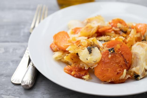 Smażona ryba dorsz ze słodkim ziemniakiem na białym naczyniu na ceramicznym tle