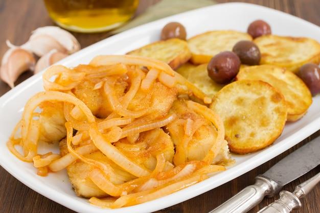 Smażona ryba dorszowa z cebulą i oliwą z oliwek na talerzu