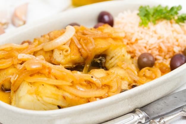 Smażona ryba dorszowa z oliwkami, cebulą i gotowanym ryżem na talerzu