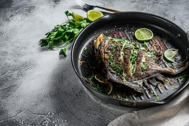 Smażona ryba dory z limonką i pietruszką na patelni. zdrowa żywność wegetariańska. szare tło