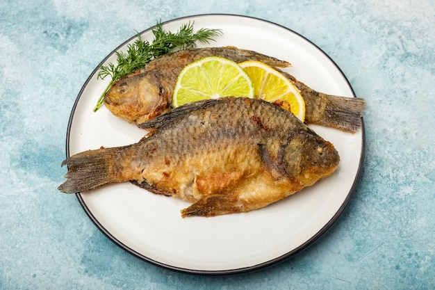 Smażona ryba karpia na białym talerzu z plasterkami cytryny i limonki, widok z góry. gotowe jedzenie. niebieskie tło