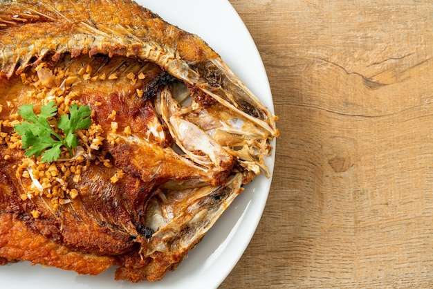 Smażona ryba okonia morskiego z czosnkiem na talerzu
