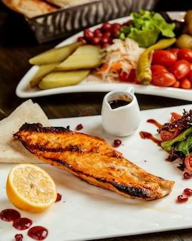 Smażona ryba podawana z sosem cytrynowym, sałatką i piklami