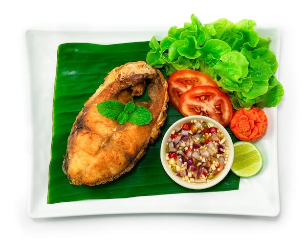 Smażona ryba w słodkim pikantnym sosie w białym talerzu na białym tle