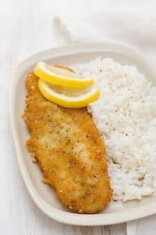 Smażona ryba z cytryną i gotowanym ryżem na naczyniu