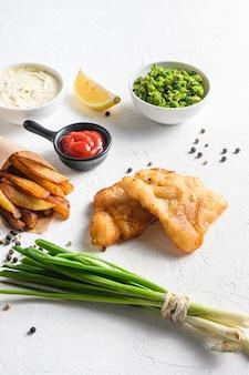 Smażona ryba z frytkami w papierowym stożku na białym tle ze wszystkimi składnikami klasyczny przepis jedzenie na wynos biały kamień teksturowane tło widok z boku ckose up details.