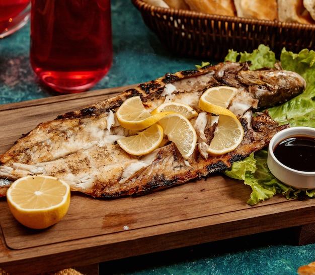Smażona ryba z plasterkami cytryny na drewnianej desce