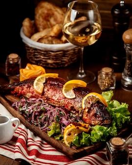 Smażona ryba z pokrojoną cebulą i cytryną