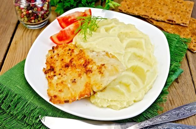 Smażona ryba z puree ziemniaczanym i pomidorami na talerzu, papryką, pietruszką, serwetką, nożem i widelcem na drewnianej desce