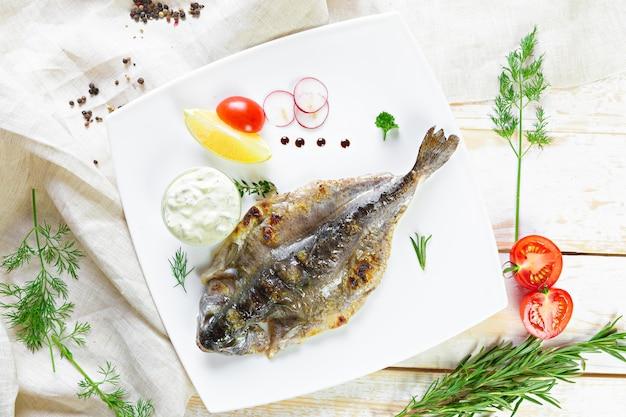 Smażona ryba z warzywami na drewnianym stole