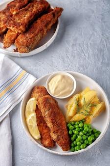 Smażona ryba ze smażonymi ziemniakami, zielonym groszkiem i cytryną