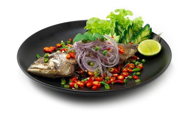 Smażona sałatka rybna z makreli z chili, cebulą, limonką ozdobiona rzeźbionym warzywem thaifood widok z boku w lokalnym stylu