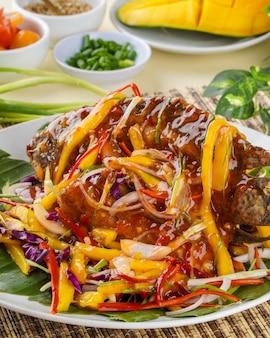 Smażona tilapia nile lub ikan nila z sosem mango indonezyjskie jedzenie i kuchnia na bambusowej tacy