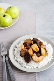 Smażona wątróbka drobiowa z jabłkami podawana z białym ryżem na talerzu