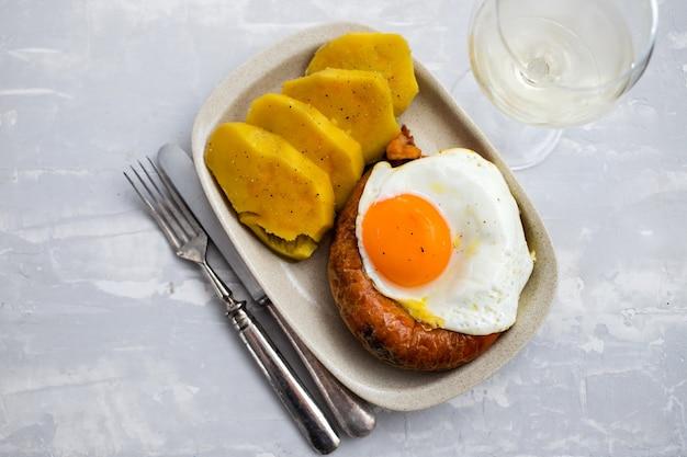 Smażona wędzona portugalska kiełbasa alheira z jajkiem sadzonym i batatem na białym talerzu