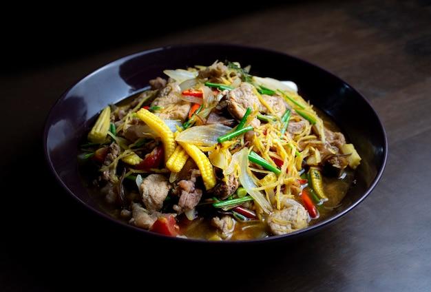 Smażona wieprzowina i imbir z mieszanymi warzywami na czarnym talerzu na drewnianym stole