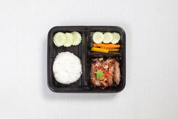 Smażona wieprzowina z czosnkiem i papryką i ryżem umieszczona w czarnym plastikowym pudełku, ułożona na białym obrusie, pudełku na żywność, tajskie jedzenie.