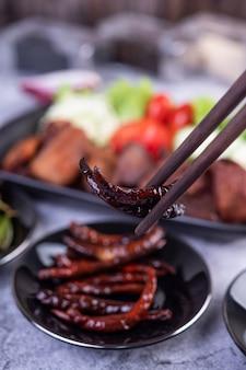 Smażona wieprzowina z sezamem umieszczona w czarnym naczyniu.