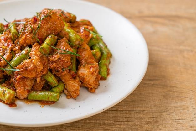 Smażoną wieprzowinę i czerwoną pastę curry wymieszać z dodatkiem fasoli, azjatyckie jedzenie