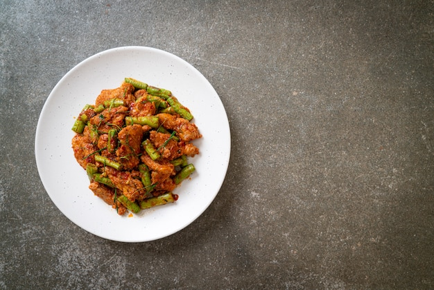 Smażoną wieprzowinę i czerwoną pastę curry wymieszać z dodatkiem fasoli