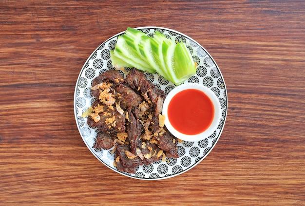 Smażona wołowina podawana z pokrojonym ogórkiem i słodkim sosem chili