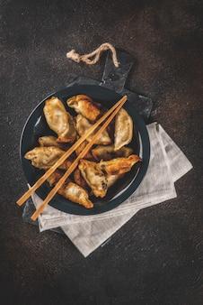 Smażone azjatyckie pierożki gyoza na ciemnym talerzu, podawane z pałeczkami i sosem sojowym