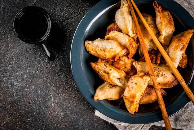Smażone azjatyckie pierożki gyoza na ciemnym talerzu podawane z pałeczkami i sosem sojowym