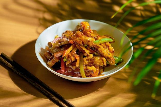 Smażone bakłażany w sosie słodko-kwaśnym z papryką i pomidorami. chińska receptura i kuchnia