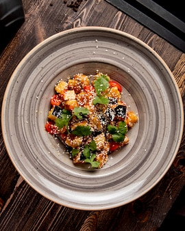Smażone bakłażany z pomidorami przygotowane w sosie i podawane z kolendrą