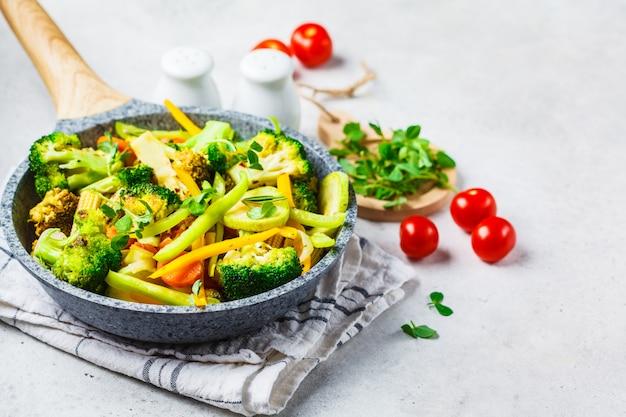 Smażone brokuły, papryka, kukurydza, cukinia i pomidory w patelni na białym tle.