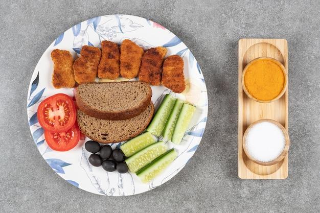 Smażone bryłki i świeże warzywa na kolorowym talerzu