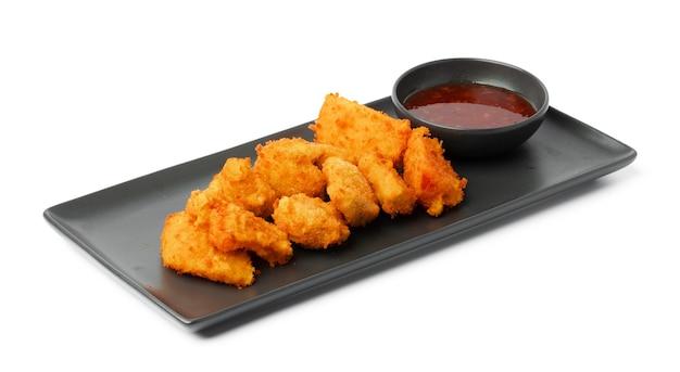 Smażone bryłki kurczaka podawane z sosem na białym tle