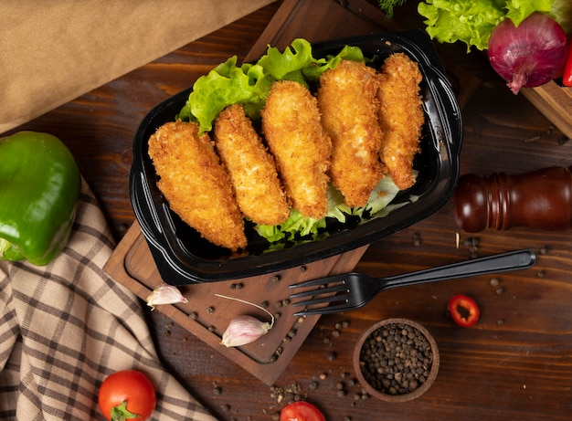 Smażone bryłki kurczaka w stylu kfc na wynos w czarnym pojemniku