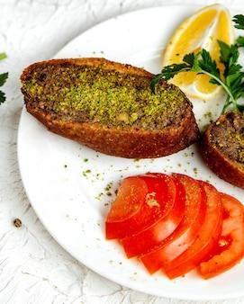 Smażone bułki zwieńczone chipsami pistacjowymi i pokrojonym pomidorem