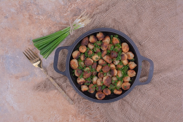 Smażone chinkali na czarnej patelni z posiekanymi ziołami.