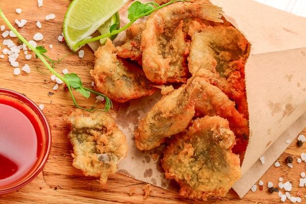 Smażone chrupiące sardele na stole z liśćmi salat. tło papieru. małe ryby w mące kukurydzianej płukanie na głębokim smażeniu.