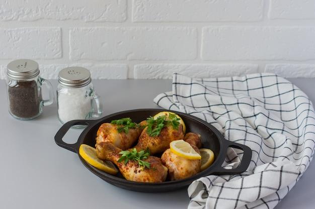 Smażone ćwiartki udka z kurczaka z ziołami, miodem, przyprawami i cytryną z bliska na patelni na stole. poziomy