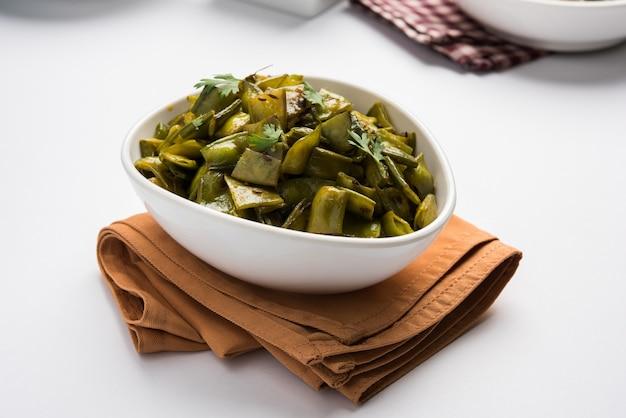 Smażone danie warzywne o nazwie flat green beans z przyprawami, podawane w ceramicznej misce, na nastrojowym tle. selektywne skupienie