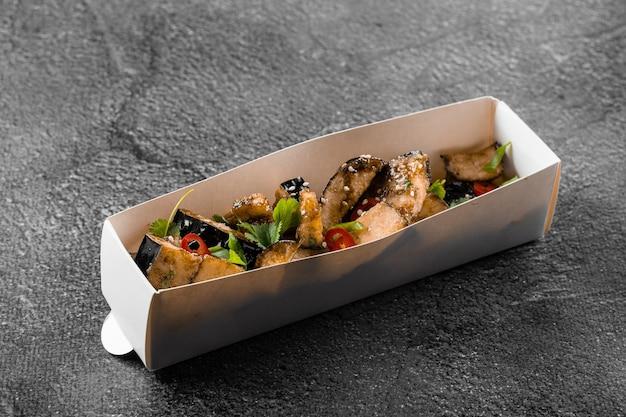 Smażone danie z bakłażana w pudełku kartonowym. dostawa jedzenia. warzywa przyozdobione kolendrą i chili na szarej powierzchni.