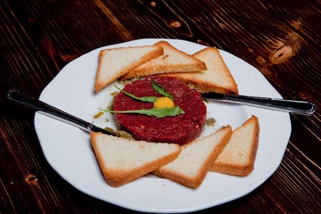 Smażone danie z mięsa tatarskiego z żółtkiem i koroną na czarnym drewnianym